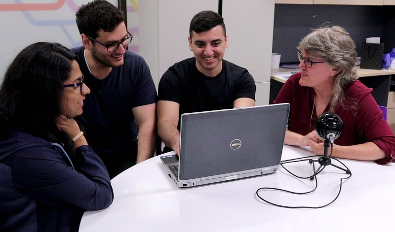 A group of students sit in front of a computer.