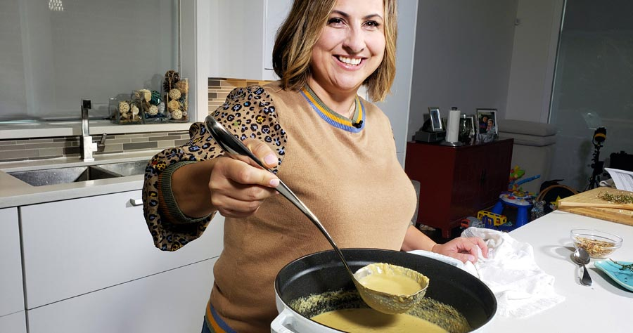 A woman spoons soup out of a pot.