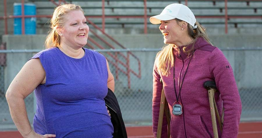 Two women smile at each other while talking on a running track.