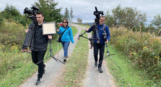 Three people walk along a trail. They are carrying television cameras.