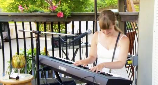 A woman sits at a keyboard.