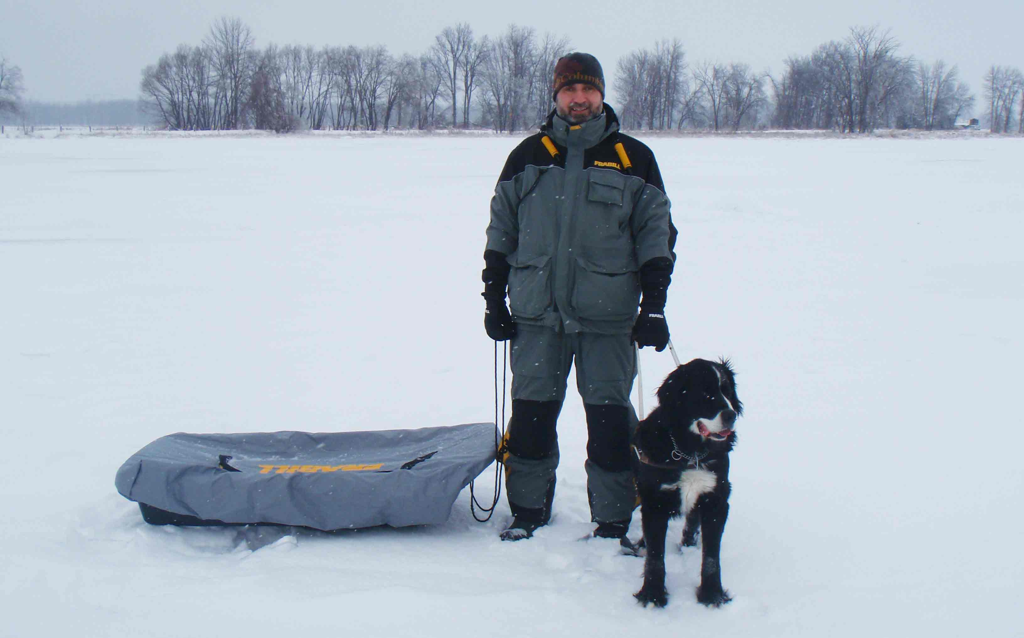 A man and a guide dog stand on a frozen lake. The man is wearing winter gear.