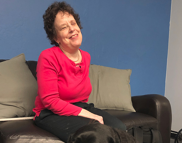 Kim Kilpatrick sits on a couch, smiling.