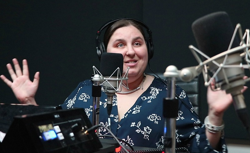 Amy Amantea smiles as she speaks into a radio microphone.
