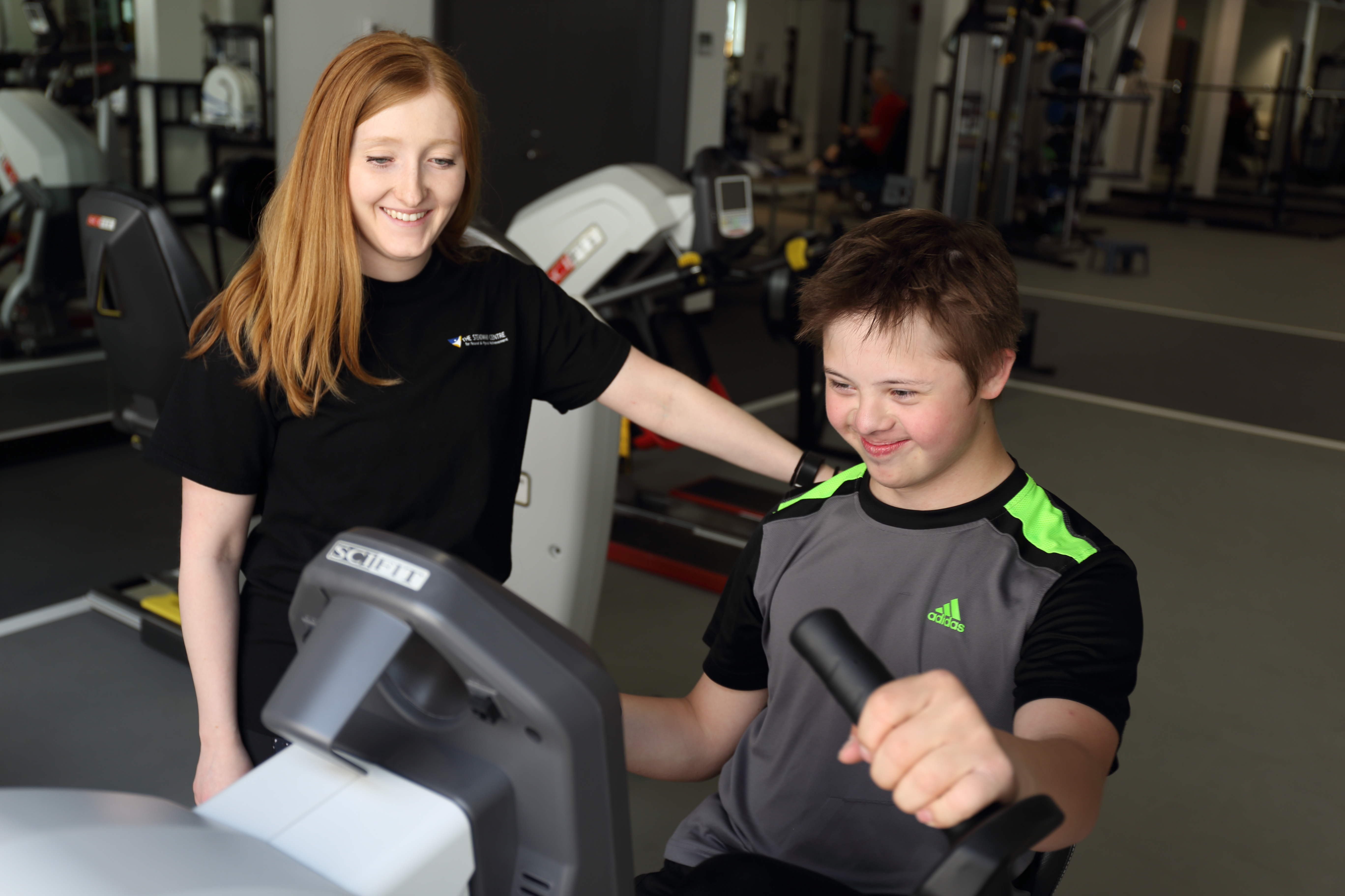 A female coach watches over a boy who is using a piece of exercise equipment.