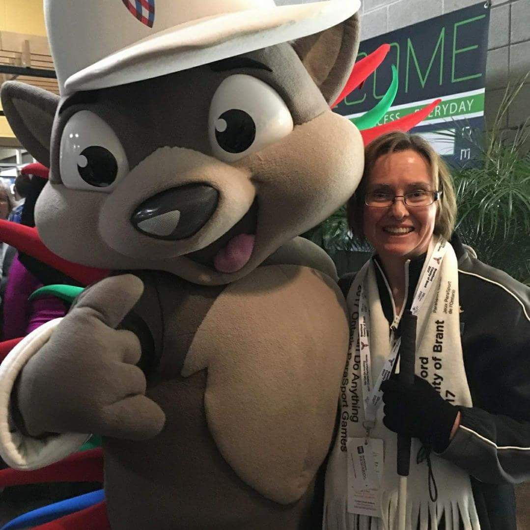 Annette poses with a cartoon mascot.