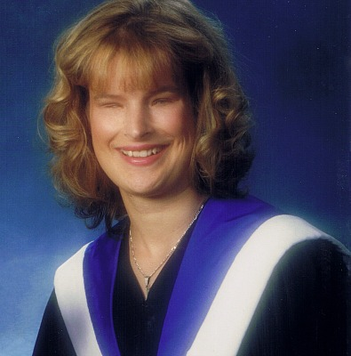 Holly Bartlett sits facing the camera, smiling. She is wearing a black graduation gown with a purple and silk ribbon draped over her shoulders.