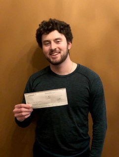 A man smiles into the camera while holding a cheque in his hand.