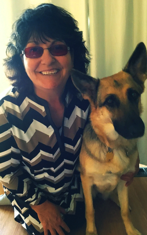 Suzanne Headshot. She poses with her guide dog, German Sheppard Emille