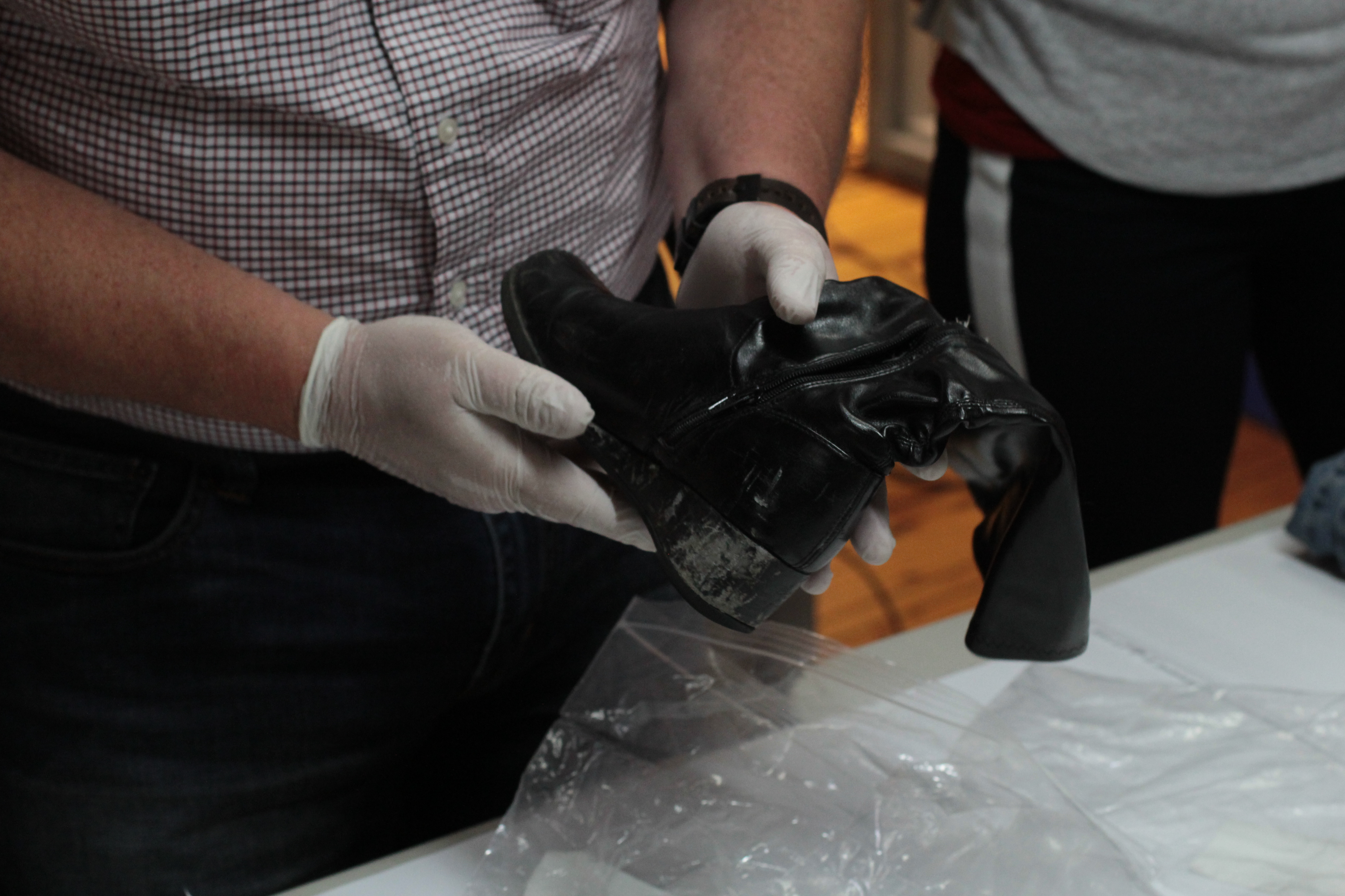 A black boot is held by two hands wearing clear rubber gloves. There is a smudge of mud on the boot's tread.