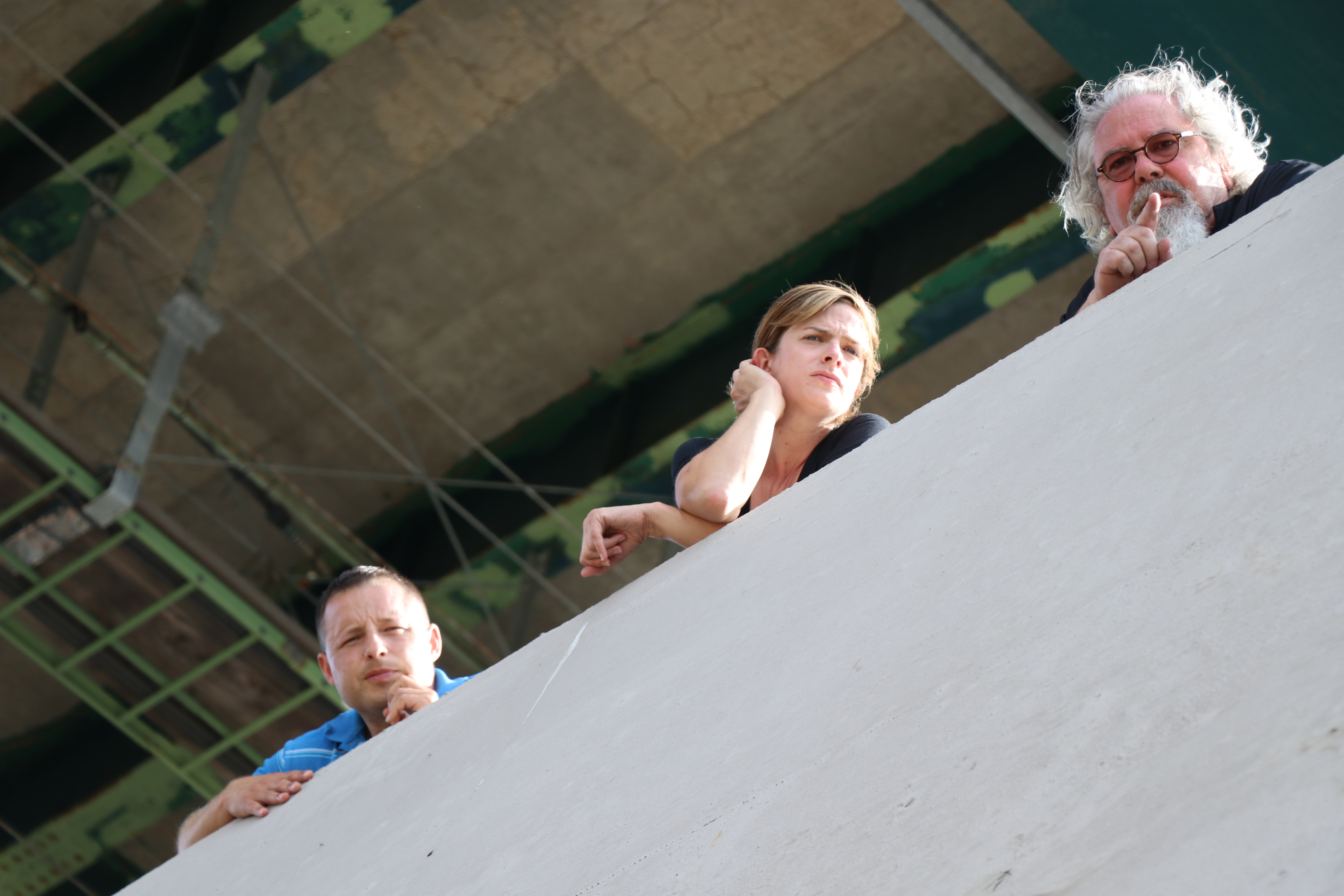 Three people look over the edge of a concrete bridge abutment.