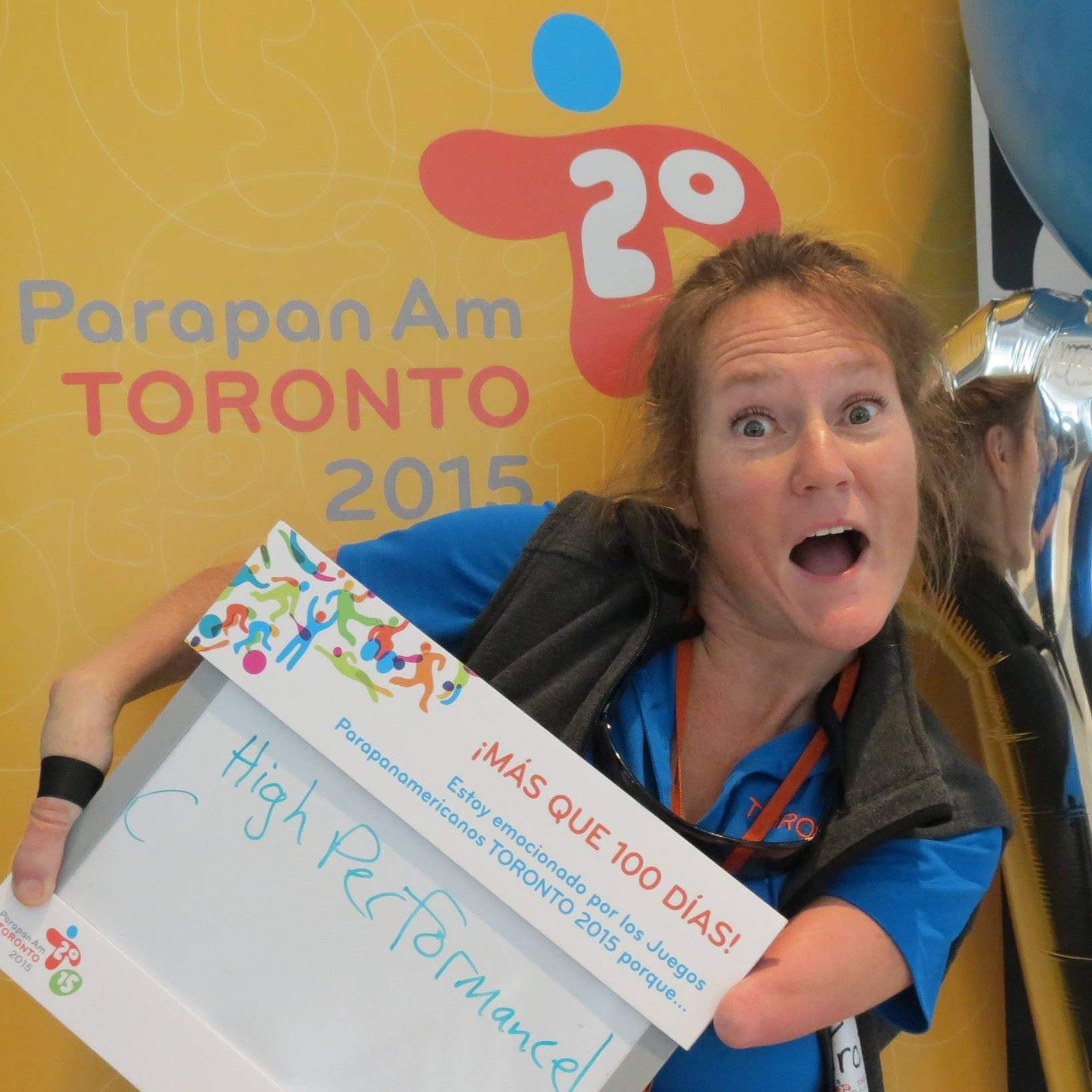 "Tracy Schmitt holds her mouth open with an excited look on her face while standing in front of a banner for the Toronto 2015 Parapan Am Games. She's holding a sign that reads, ""High Performance."""