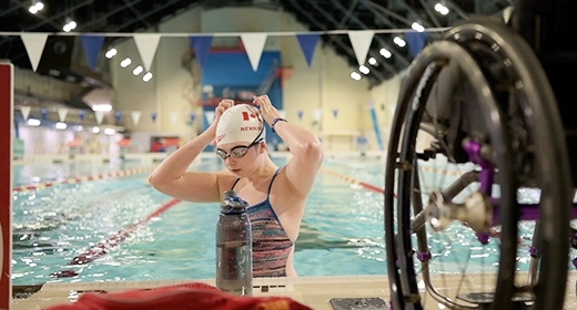 A woman stands in a swimming pool, adjusting her cap.