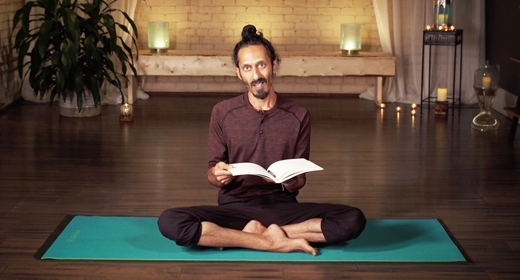 Kevin Naidoo sits cross-legged on a rug, holds a book
