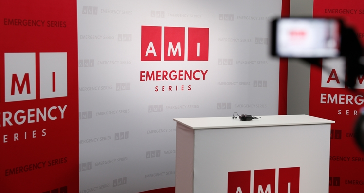 An empty television studio with the AMI Emergency logo displayed.